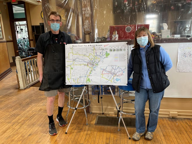 Lucie Fortin (right), a community planner and landscape architect for the Mannik & Smith Group, and Scott Goocher from Jack's Bicycle pose with a map of the proposed bike trails for Monroe County.