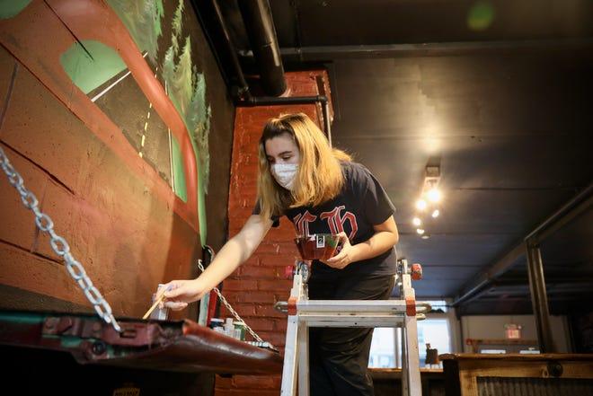 Midlakes junior Elena Graf creates a mural at Smokin' Tails Distillery in Phelps.