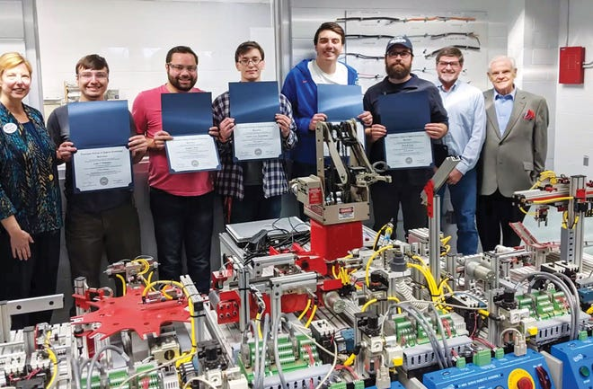 From left are Danice Turpin, TCAT-Harriman president; electricity job training program students Luke Whitmire, Joseph Sears, Gavin Drummond, Brian Charles, and Brett Coots; Buddy Tharp, Residential/Industrial/Commercial Electricity program instructor; and state Sen. Ken Yager. The students are enrolled in Tharp's class. In front is special manufacturing equipment used in the training.