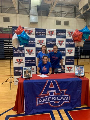 Vanguard's Sarah Milbrandt poses with parents Kristen, left, and Eric Milbrandt as she signs her national letter of intent to swim at American University.
