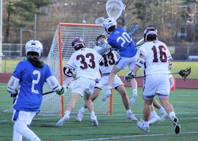 Portsmouth goalie Skyler Mikalietes (48) defends a wrap-around attempt by Oyster River's Jacob Failla (20) while Portsmouth's Max Diep (33) closes in during the fourth quarter of Thursday's Division II boys lacrosse game. Mikalietes made six saves for the shutout.