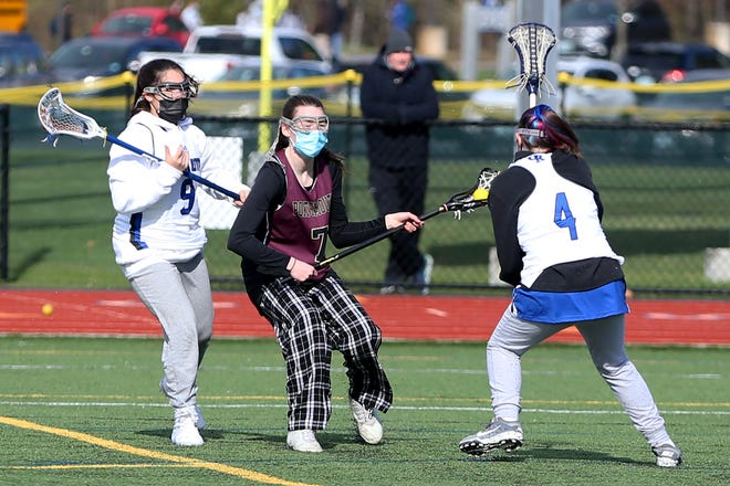 Portsmouth's Skye Macleod, center, splits a pair of Oyster River defenders during Thursday's Division II girls lacrosse game at Oyster River.