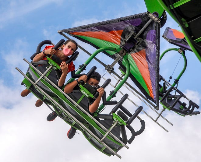 Left to right: Arista Keith, 13, and Malvin Vega, 7, of Palm Springs soar through the air on the Cliff Hanger ride on the last day of the South Florida mini-fair Jan. 31. DAMON HIGGINS / PALM BEACH POST