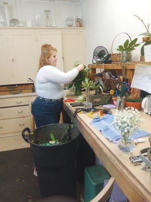 Deborah Alice, an employee at The Flower Shoppe, works on a special arrangement.
