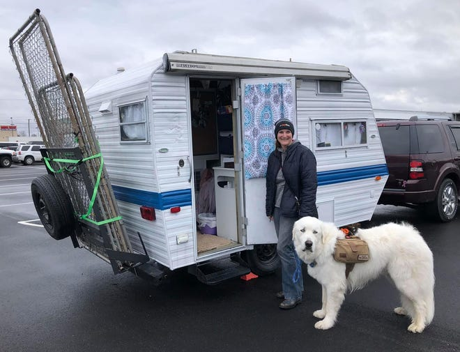 """Harvest Hosts member Destiny Sommer and her 165-pound Great Pyrenees Falkor pose for a photo beside """"Penelope"""" their 1989 10-foot Scotty parked at the Keystone Truck and Tractor Museum in Colonial Heights, Va. on February 27, 2021."""