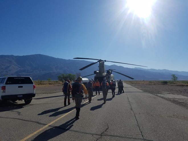 Search and rescue personnel head toward a Chinook helicopter to begin to look for a missing hiker near Mt. Whitney on Tuesday.