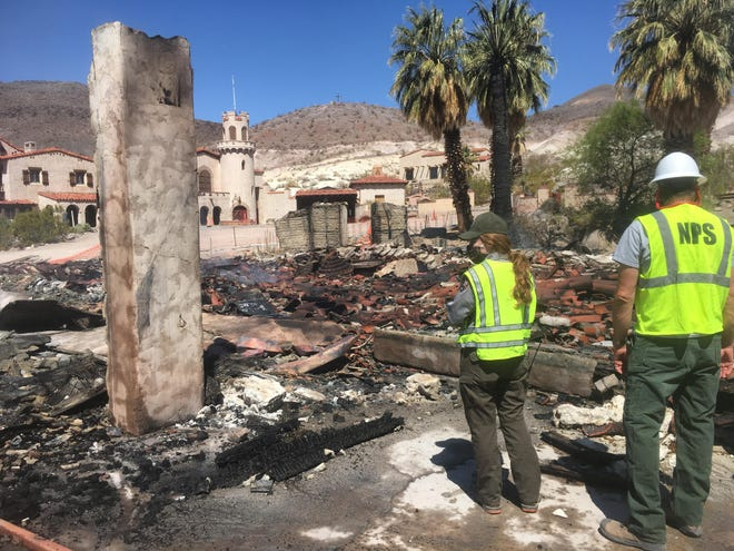 Rangers stand near the remnants of the historic garage in the Death Valley Scotty Historic District. The main house, in the distance, did not incur any damage.