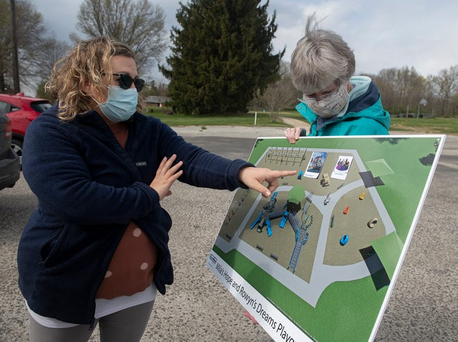 Fields Playground Group President Susan Monegan holds a rendering of the all-inclusive playground as social media director Amanda Phipps explains certain park equipment.