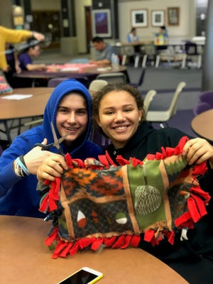 Aja Shriver (left) and Mitchell Brown (right) make blankets to donate to hospitalized children.