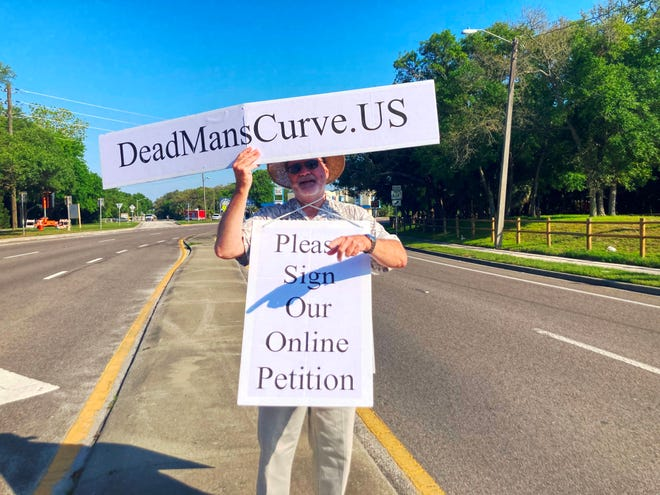 St. Augustine resident Bruce Bates protests for safety changes at the curve on Anastasia Boulevard around Red Cox Drive.