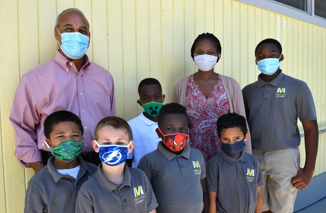Louis Parker, new interim CEO of Visible Men Academy, left, poses for a photograph with principal Tiffany Mickens and a group of students during an afternoon activity break.