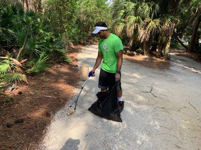 Florida Power & Light employee Muneeb Majeed picks up litter in North Port in honor of Earth Day with the help of a Power to Clean kit he received from FPL.