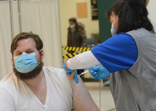 Will Tate, 32, of Norwich gets his first Moderna COVID-19 vaccination from Laura Stay RN Friday at the Rose City Senior Center in Norwich where walk-ins were welcomed as well as people with appointments. [John Shishmanian/ NorwichBulletin.com]