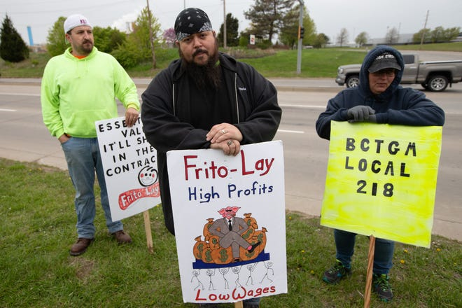 Dan Negrete, middle, chief shop steward and on the contract negotiations committee, stands alongside Cyrus Moore, left, a Frito-Lay employee for more than two years, and Amanda Gallaway, right, an employee for 15 years, during a picket Friday outside of the Topeka plant, 4236 S.W. Kirklawn Ave.