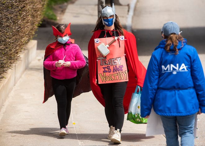 """Elivia Thomas, 10, enjoys ice cream while dressed for """"superhero day"""" Friday while walking the St. Vincent Hospital picket line in Worcester with her mom, Sondra, who's a nurse."""