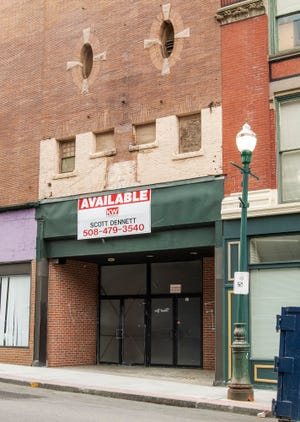 The former theater building at 17-27 Pleasant St. has had a handful of names over the entrance through the years, the latest that of a real estate agent.