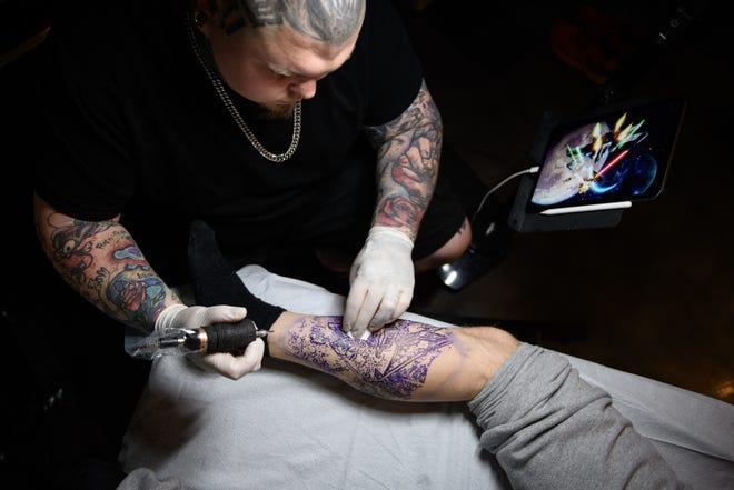 Fayetteville tattoo artist Jonathan Dump works on putting a Star Wars tattoo on Lee Shelton's leg on Thursday, April 22, 2021, at Best Ink of Fayetteville.