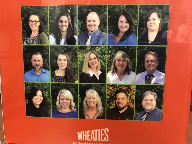 """The back of the commemorative """"Wheaties"""" cereal box features photos of the district's food and nutrition services support team."""