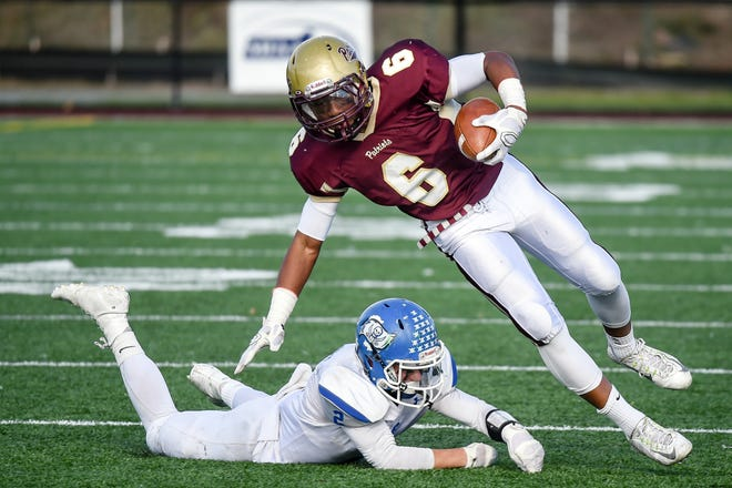 Concord-Carlisle High School senior Jovan Grant avoids a tackle by Bedford High School senior Matt Timpiero during the annual Thanksgiving Day game in Concord in 2015.