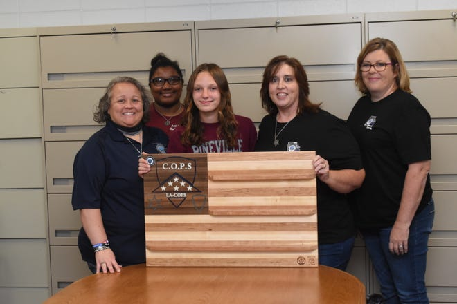 Annalee Stevens (center), a woodworker, presented a wooden challenge coin holder flag she created to Louisiana C.O.P.S. board members Jada Breaux (left), president; Amber Sylvester, second vice president; Tanya Johnson, vice president; and Kim Stuckey, treasurer. The flag was created as part of Forest 2 Home's F2H Givea Back campaign. Annalee is a brand ambassador for the company that caters to small woodworkers like Annalee.
