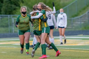 Reynolds midfielder Addie Porter (right) hugs Kennedy Porter after the sisters combined for an equalizer Wednesday against Reynolds.