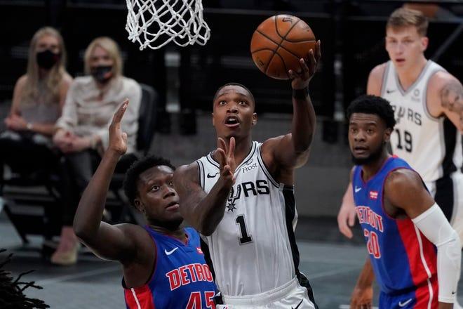 Guard San Antonio Spurs Lonnie Walker IV (1) melaju ke ring melewati penyerang Detroit Pistons Sekou Doumbouya (45) selama paruh pertama pertandingan bola basket NBA di San Antonio, Kamis, 22 April 2021.