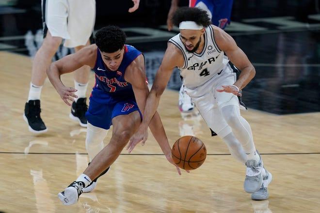 Guard Detroit Pistons Killian Hayes (7) dan guard San Antonio Spurs Derrick White (4) mengejar bola lepas di babak kedua.