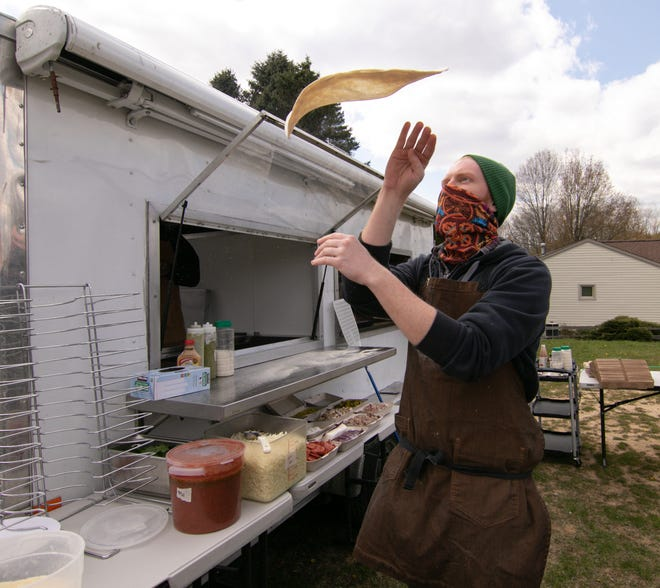 Jake Hanson of Captain's Wood Fired Pies tosses a New Haven-style crust Thursday, April 22, 2021 in a subdivision on Scenic Drive in Brighton Township.