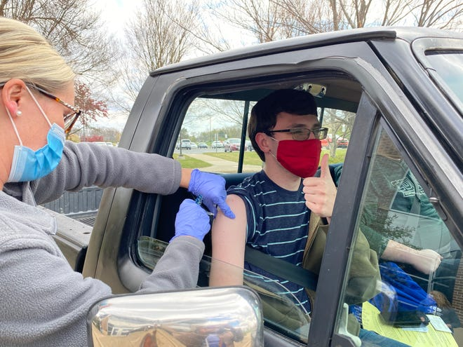 Marion Public Health nurse Elizabeth Oldham inserts a dose of the Pfizer vaccine into the arm of John Hammon of Marion. The 23-year-old visited the agency's drive-thru clinic at The University of Ohio State at Marion Thursday, April 22, 2021.