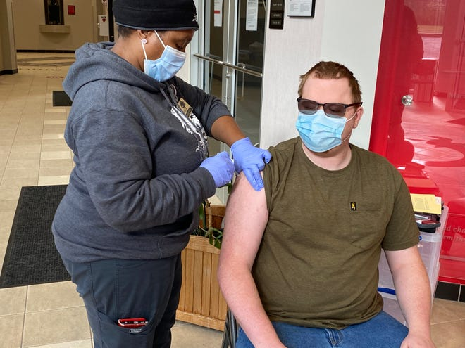 Marion Public Health nurse Laguel Howell gives the COVID-19 vaccine to Adam Young, 21, of Candlewood Lake.
