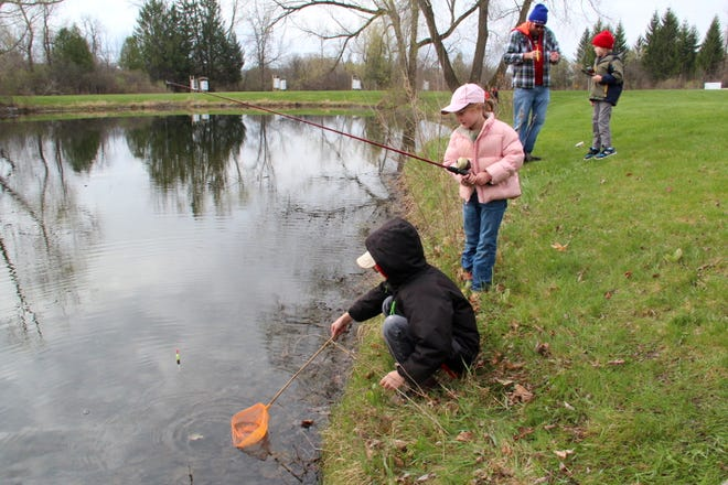 Quintin Witt of Menomonee Falls prepares to net a bluegill for his sister Kaylee at a fishing clinic at Daniel Boone Conservation League in Hubertus. Members of the Milwaukee chapter of Great Lakes Sport Fishermen and the Wisconsin Fishing Club partnered with Daniel Boone to run the clinic last Sunday.