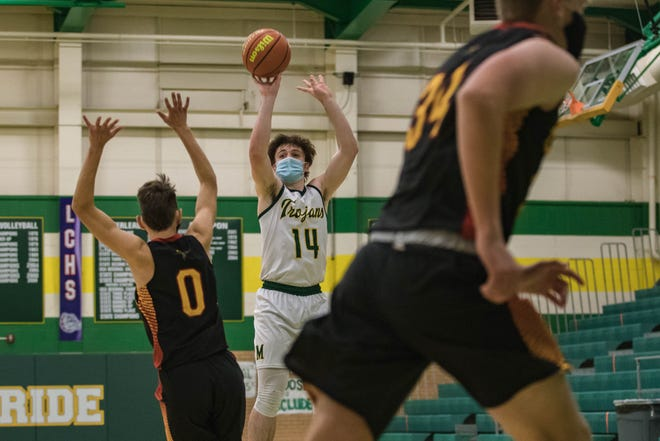 Cameron Sowards (14) shoots as the Mayfield Trojans face off against the Centennial Hawks at Mayfield High School in Las Cruces on Thursday, April 22, 2021.