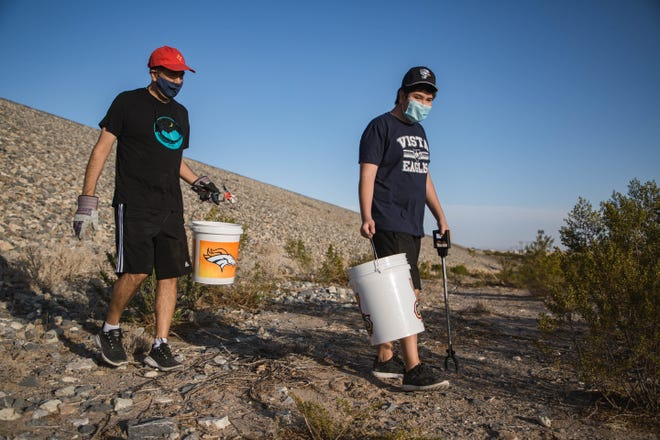 Jeffrey Silva and his son Zane clean up the base of the Las Cruces Dam near Planet Fitness in Las Cruces on Thursday, April 22, 2021.