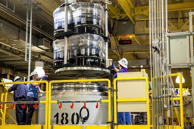 Waste handlers take radiological readings as a crane lifts containers from a TRUPACT-II cask in the contact-handled waste bay at the Waste Isolation Pilot Plant. The DOE facility has resumed accepting shipments and processing waste after a two-month annual maintenance outage.