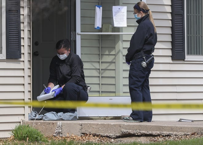 Investigators work the scene Friday in the 5600 block of Ferge Street in Weston. Police responded to a report of a woman needing help and fired their weapons when confronted by an armed man, who was in critical condition Friday morning at a local hospital. Police found a woman dead at the scene.