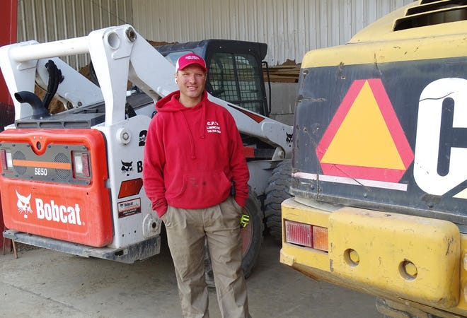 Chad Parker stands in the garage of C.P.'s Landscape and Outdoor Supply. Heavy equipment is left behind at the Perry Township shop due to fewer employees, he said. Parker has spent thousands of dollars on advertising to recruit new employees.