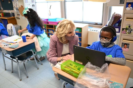First Lady Jill Biden speaks with a student as she tours Benjamin Franklin Elementary School in Meriden, Conn., on March 3, 2021. She was visiting to help reassure school districts they can reopen safely during the pandemic.