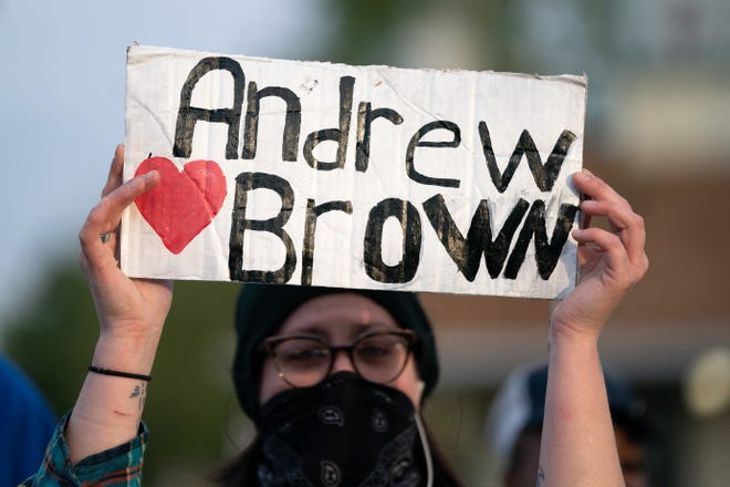 A demonstrator holds a sign for Andrew Brown Jr. during a protest march on April 22, 2021 in Elizabeth City, North Carolina. The protest was sparked by the police killing of Brown on April 21.