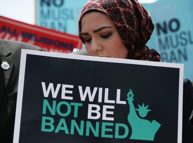 A woman participates in a demonstration against President Donald Trump's travel ban outside the U.S. Supreme Court following an immigration ruling on June 26, 2018, in Washington, D.C.