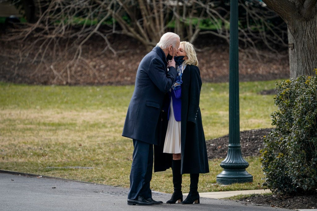President Joe Biden lowers his mask to kiss wife Jill Biden as he walks to Marine One on the South Lawn of the White House for a trip to Walter Reed medical center to visit with wounded service members on Jan. 29, 2021.