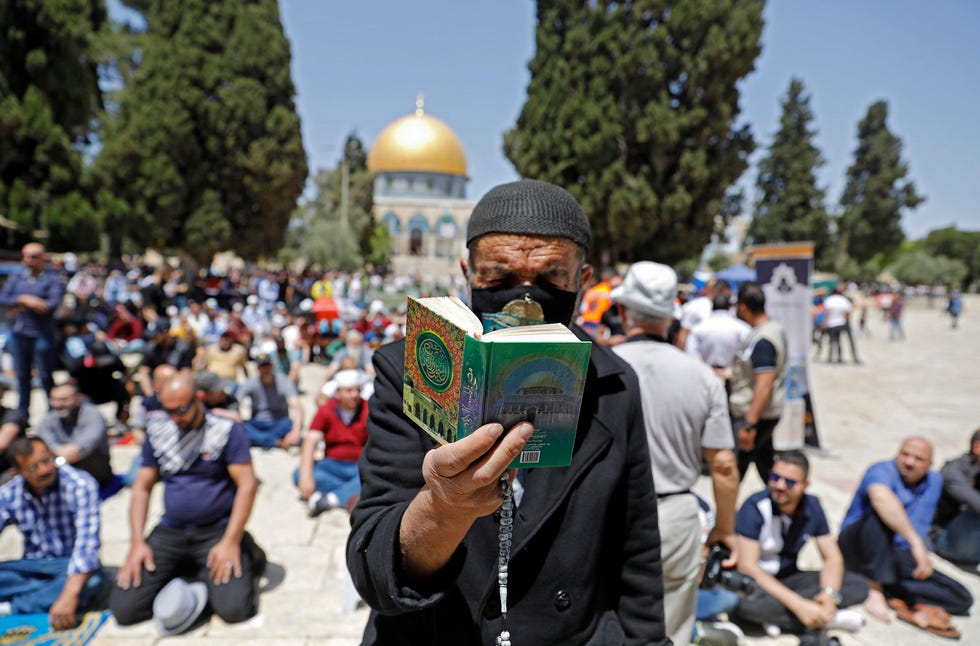 A man reads the holy Koran as Palestinians gather during the second Friday prayers of the Muslim fasting month of Ramadan, outside the Dome of the Rock at the Al-Aqsa Mosque compound, Islam's third holiest site, in Jerusalem's Old City, on April 23, 2021.