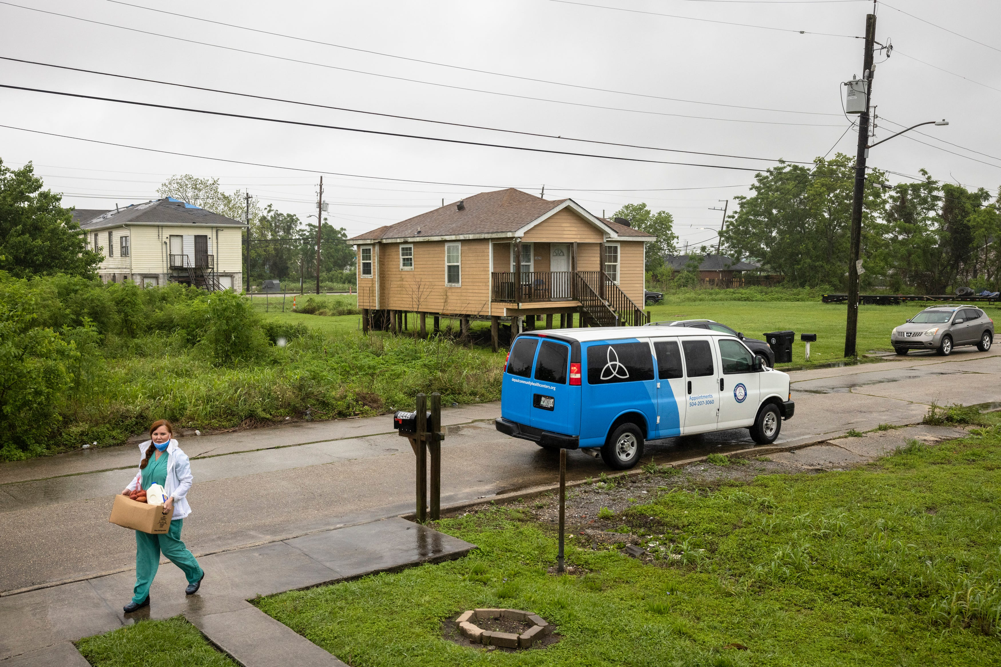 Nurse practitioner Sophia Thomas delivers food to a resident while going door-to-door attempting to administer COVID-19 vaccines in New Orleans on Saturday, April 17, 2021.