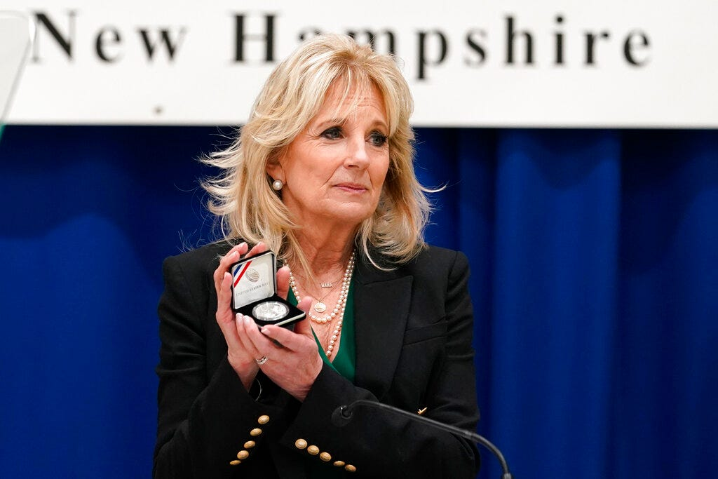 """First lady Jill Biden holds a Christa McAuliffe commemorative coin she received as she speaks at Christa McAuliffe School in Concord, N.H., Wednesday, March 17, 2021, to pay tribute to the New Hampshire woman chosen 35 years ago to be America's """"Teacher in Space.""""(AP Photo/Susan Walsh, Pool)"""