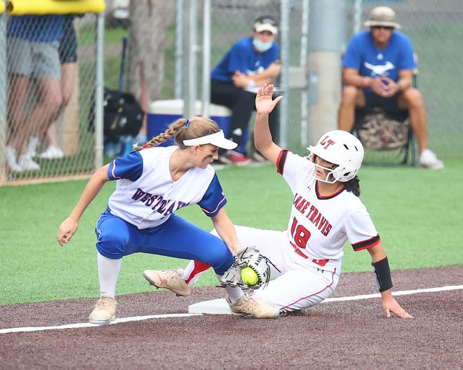 Lake Travis runner Ava Ammerman slides in safely at third base in the first inning against Westlake April 23 at Westlake High School. Lake Travis defeated Westlake with a 15-0 run-rule final.