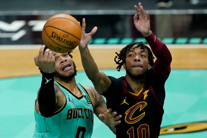 Charlotte Hornets forward Miles Bridges, left, is fouled by Cavaliers guard Darius Garland during the second half of the Hornets' 108-102 win Friday night. [Chris Carlson/Associated Press]