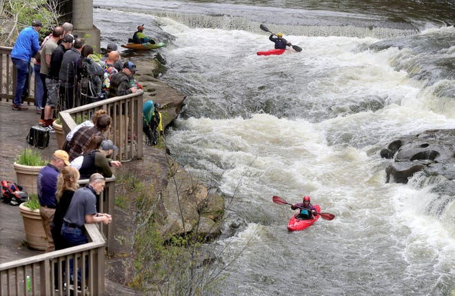 Spectators line the rocky banks to get a glimpse of kayakers participating in the Cuyahoga Falls Fest on the white water of the Cuyahoga River behind the Sheraton Suites in April in Cuyahoga Falls. The city is in line to receive a $50,000 grant from the National Endowment for the Arts to support its River in the City project.