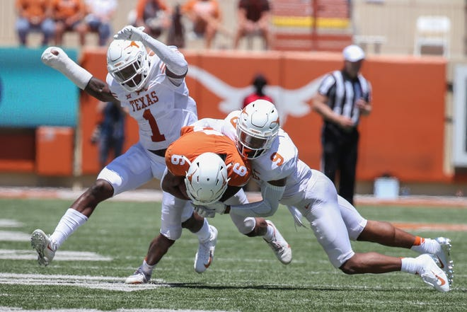 Texas defensive back Josh Thompson tackles wide receiver Joshua Moore in the first quarter of Saturday's Orange-White game at Royal-Memorial Stadium.