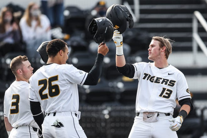 Missouri's Cameron Swanger (13) celebrates with teammates Torin Montgomery (26) and Tre Morris (3) after hitting a two-run home run during a game against Georgia on Friday night at Taylor Stadium.