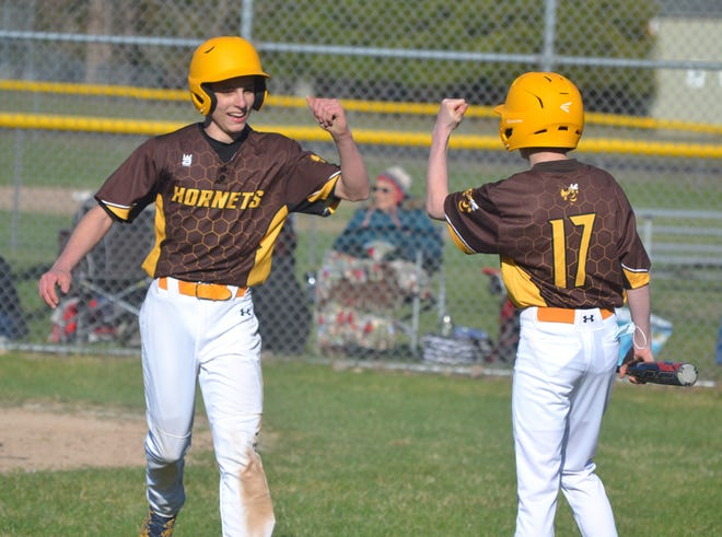 Pellston freshman Kenny Crawford (left) gets congratulated by fellow freshman Jack Schmalzried (17) after Crawford scored a run against Johannesburg-Lewiston in a doubleheader on Friday, April 16. The two freshmen played big roles in helping the Hornets earn a split against Lake Linden-Hubbell in Pellston on Friday.