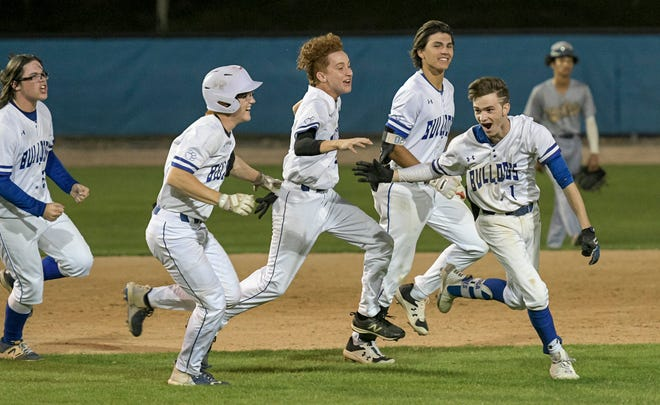 MDCA's Dominic Jones (1) is cheered by his teammates after batting in the winning run in Friday's game against Eustis in Mount Dora. [PAUL RYAN / CORRESPONDENT]